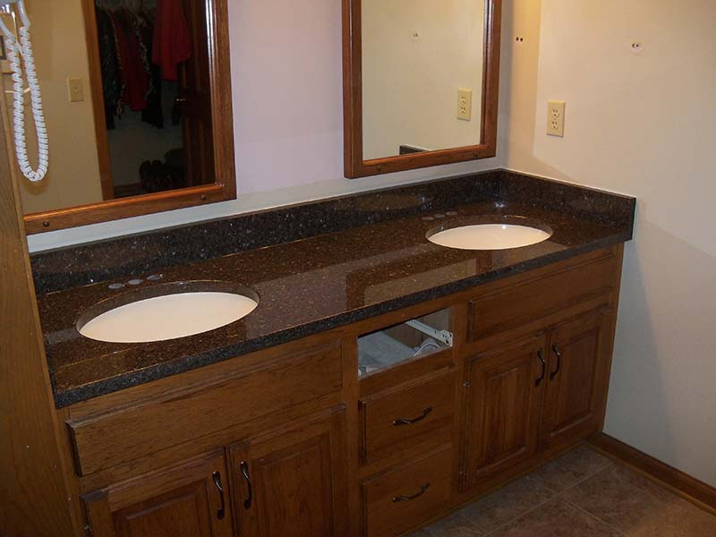 Brown Pearl aka Imperial Coffee Granite bathroom counter with double sinks over medium wood toned cabinets.