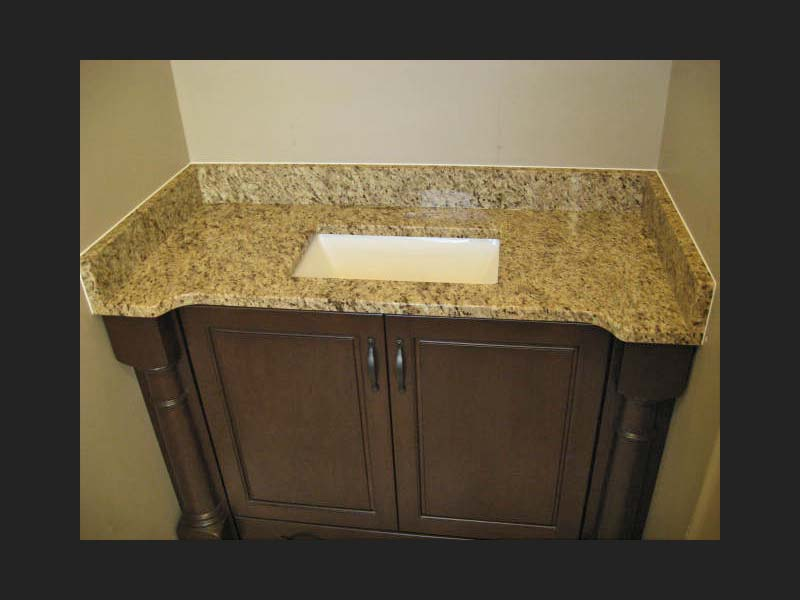 Giallo Ornamental Granite bathroom counter over a dark wood vanity with a square sink.