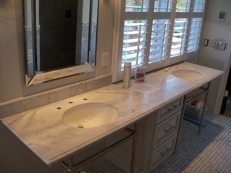 Italian White Marble with double sinks over white cabinets.