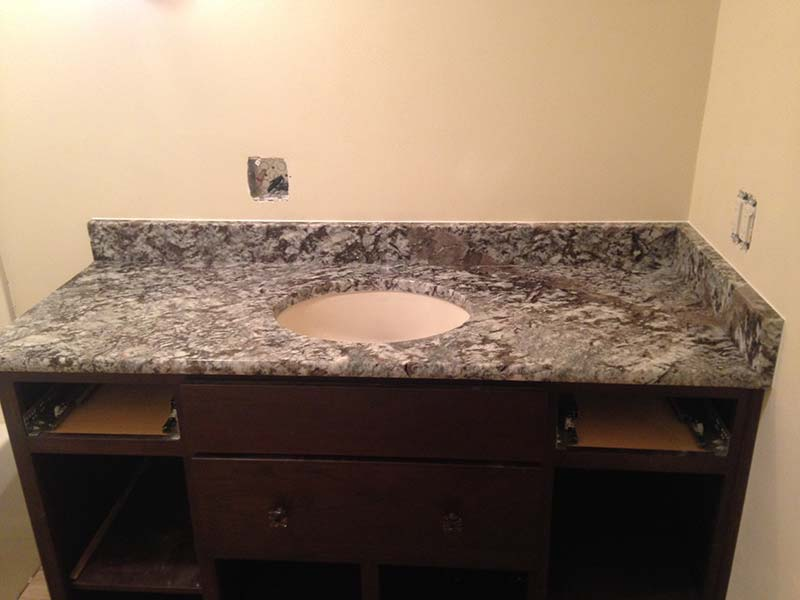 This Lennon Granite bathroom counter ties together the light walls and high contrast dark brown bathroom vanity.