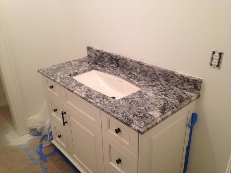 This Lennon Granite bathroom counter provides some dark contrast in this light colored bathroom.