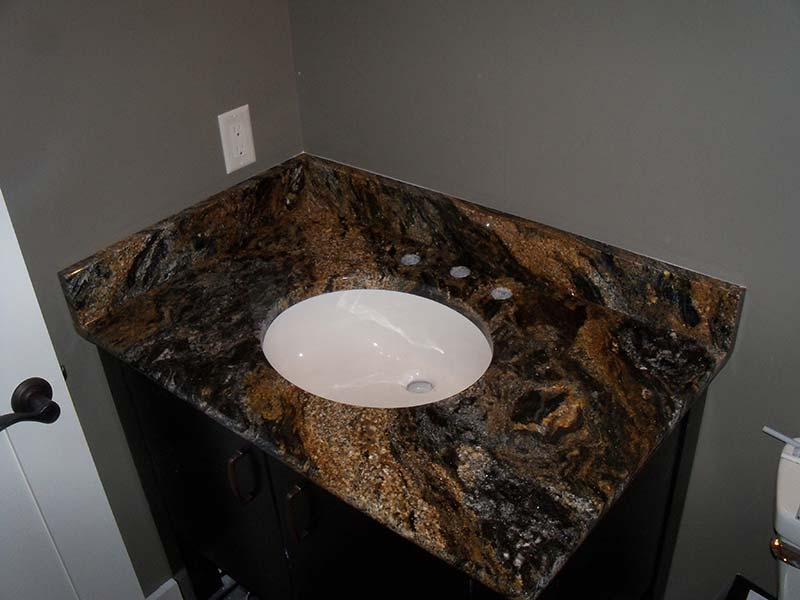 This bathroom counter of Magma Granite shows the high contrast colors of gold, dark grey, off white, and black.
