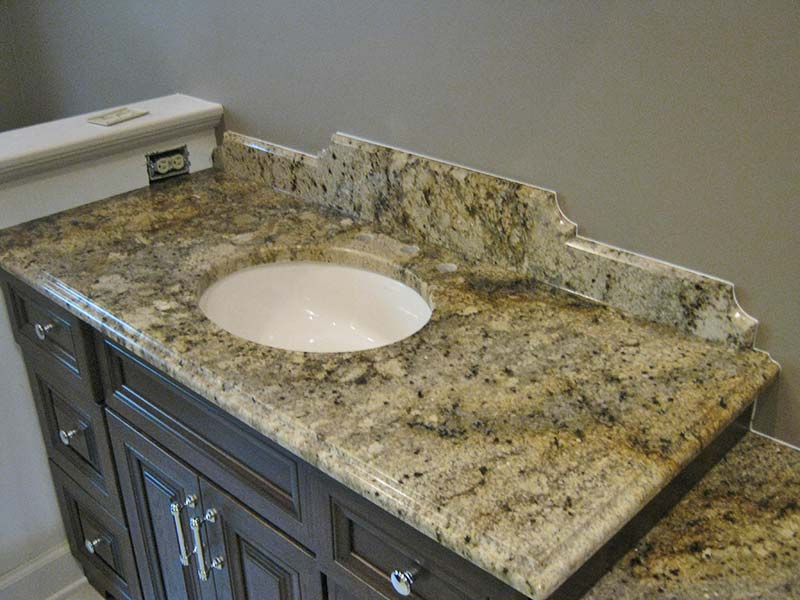 The earthtone shades of Spring Beige Granite really pop over the dark brown cabinets.