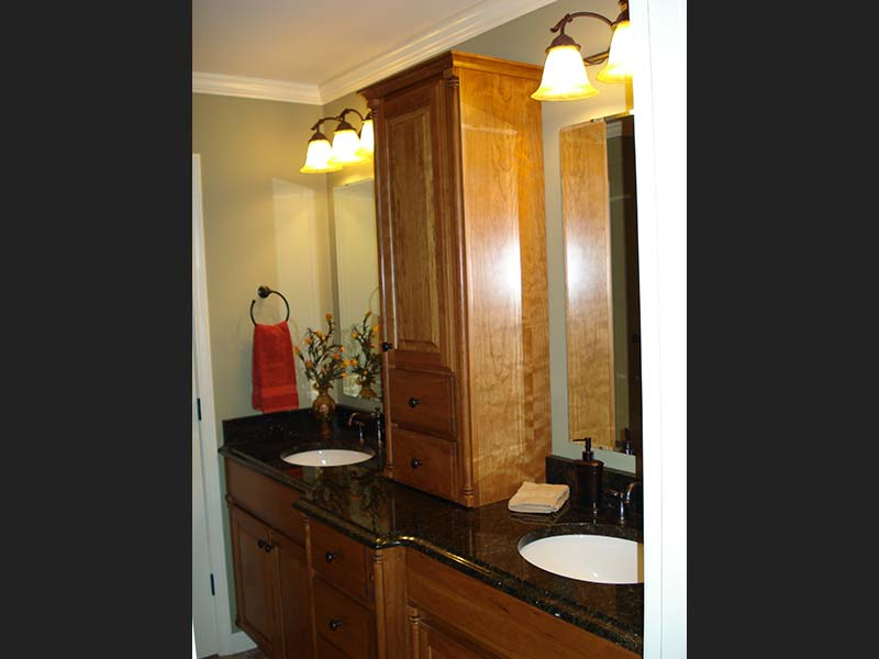 Uba Tuba Granite counter with double sinks shines agains medium-dark wood toned cabinets.