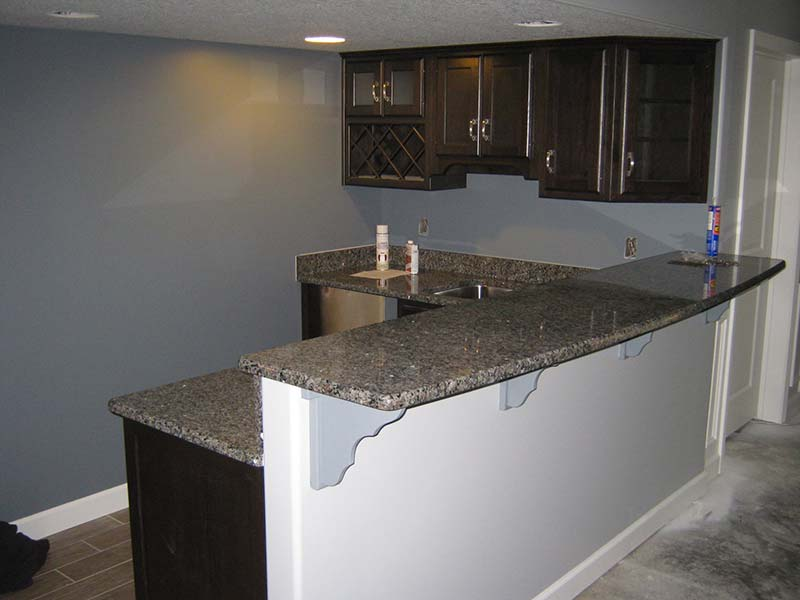 Caledonia Granite counter, wet bar, and sink over brown and white cabinets.