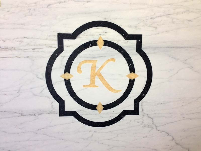 Bianco Carrera Marble with monogram inlay in gold and black.