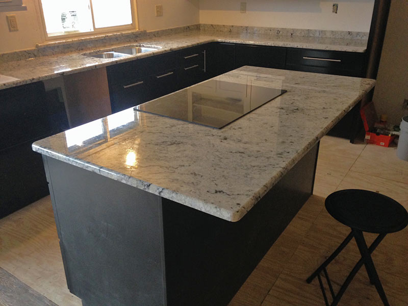 Colonial White Granite kitchen counter and island with Gray cabinets.