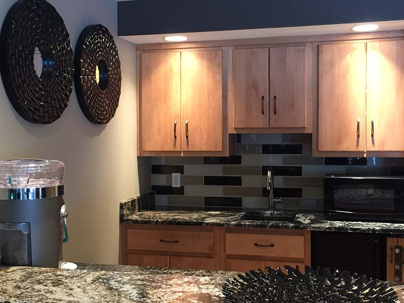 Diamond Wave Granite kitchen counter with medium wood toned cabinets and black accents.