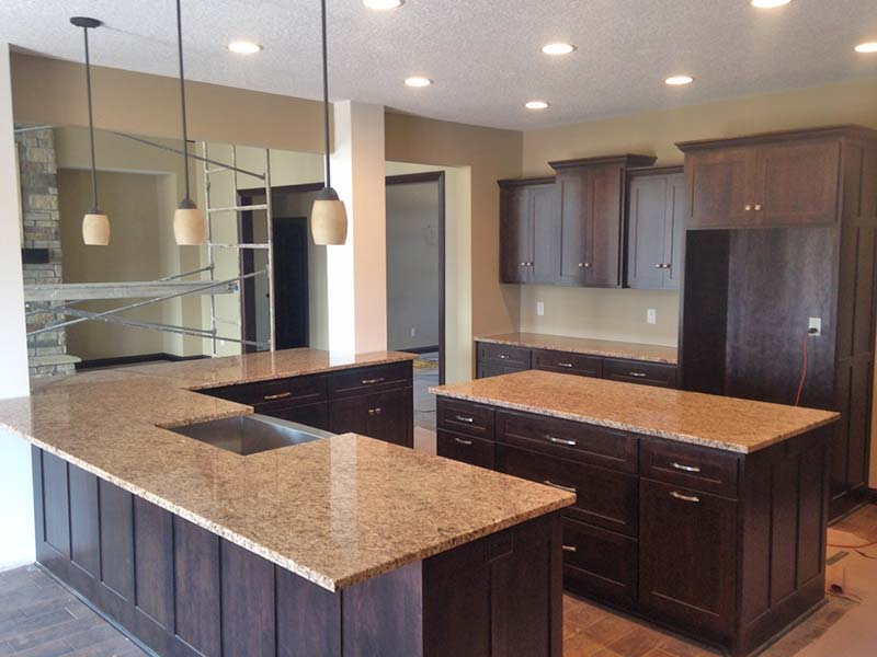 Giallo Ornamental Granite kitchen counters and center island show off this large kitchen with dark wood cabinets.