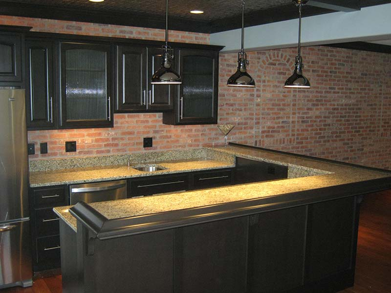Juperana Gold Granite kitchen island and counters dark cabinets.