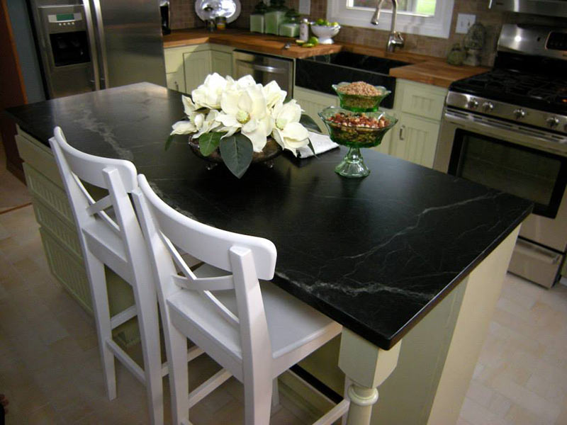 Oiled Black Soapstone playing up the contrast against white cabinets and chairs.