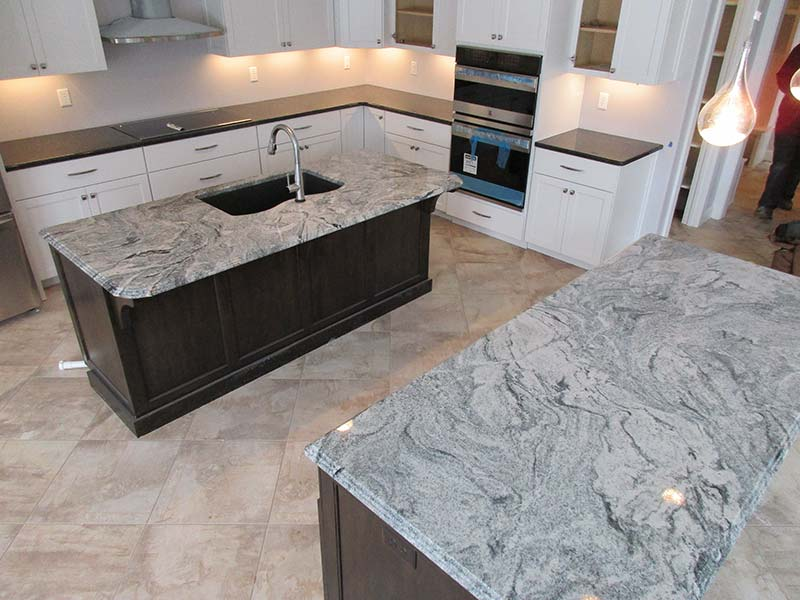 Viscont White Grante counters and kitchen island with brown and white cabinets.