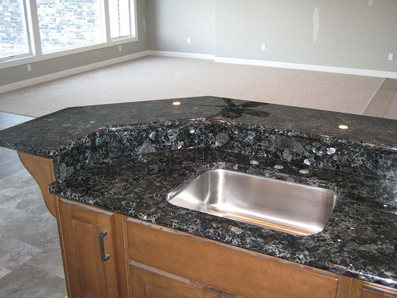 Volga Blue Granite kitchen island sporting a stainless steel sink.