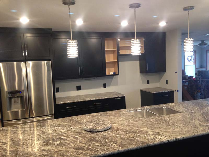 White Thunder Granite kitchen counter and dark brown cabinets, nice.