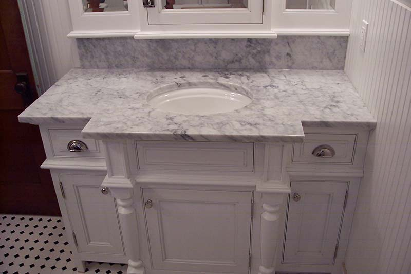Italian White, or Carrara Marble bathroom counter looking very classical over a white columned vanity.