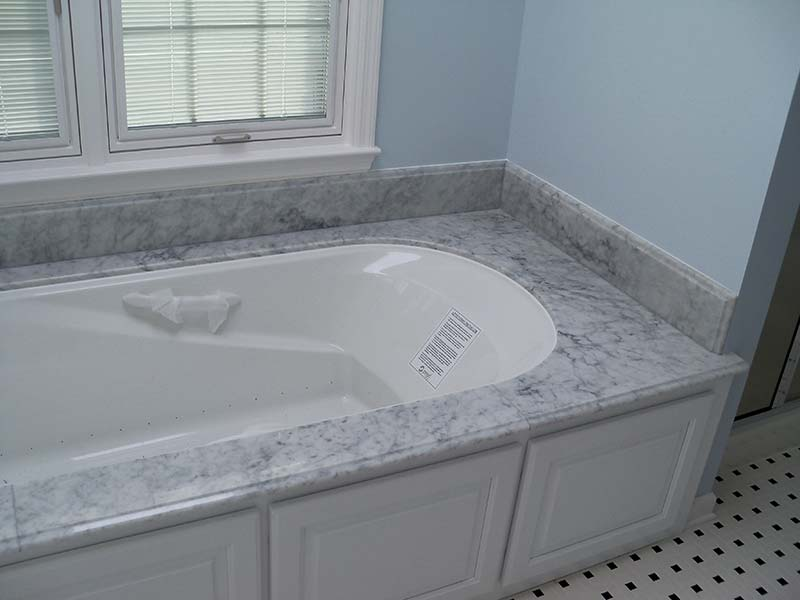 Italian White Marble tub deck over white cabinets contrasted by light blue bathroom walls.