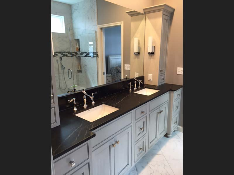 Dark oiled Soapstone counter with contrasting white double sinks looks great above the light bathroom vanity.