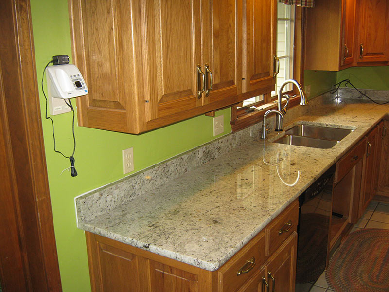 Colonial White Granite kitchen counter with medium brown cabinets.