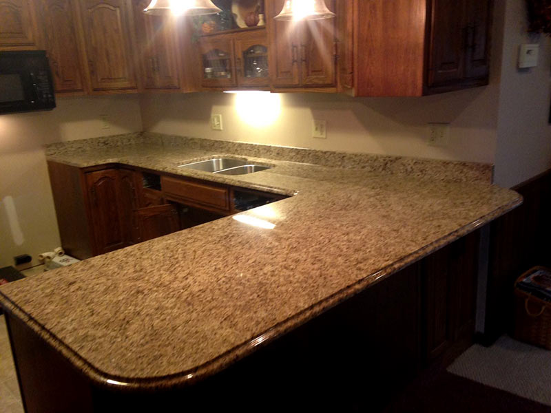 Earthtones create a warm inviting kitchen with Giallo Ornamental Granite and medium brown cabinets.