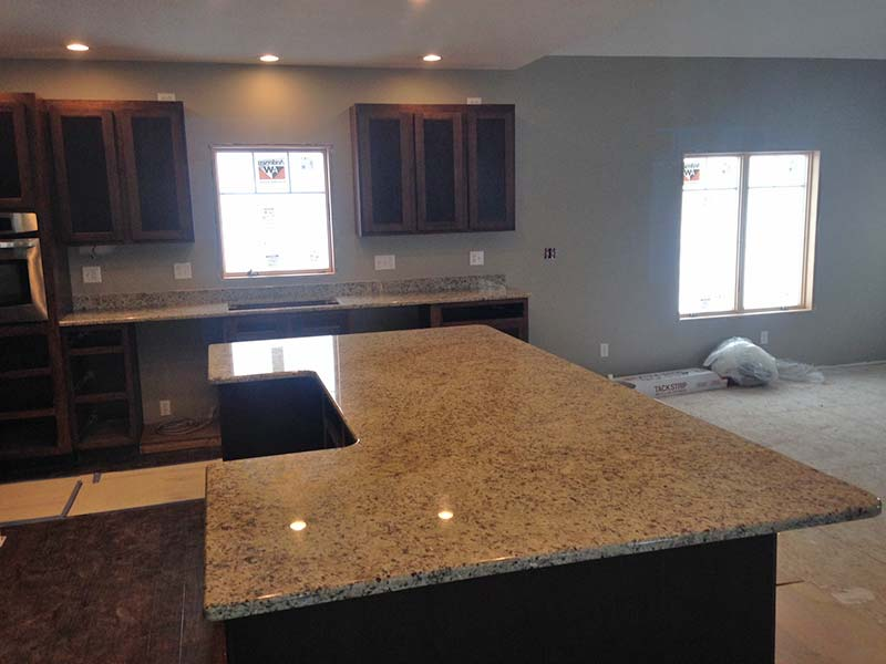 Juperana Gold kitchen island and dark cabinets.