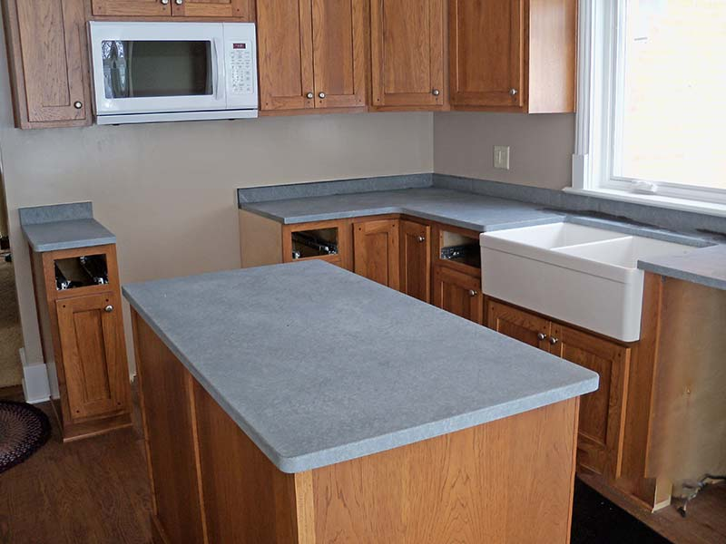 Black Soapstone kitchen island and counter, not oiled, over golden oak cabinets