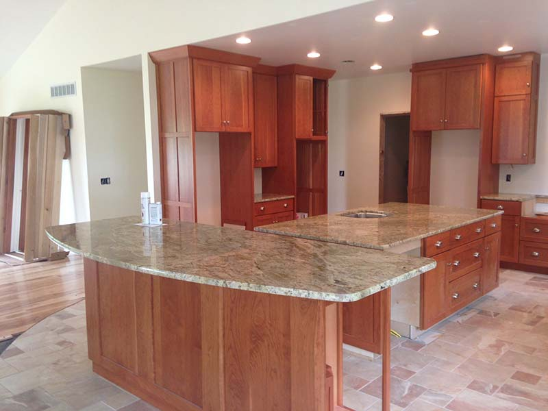 Typhoon Bordeaux Granite kitchen counter and island with warm medium toned cabinets.