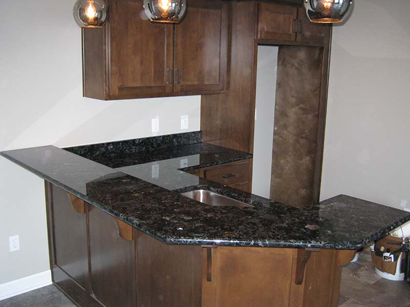 Volga Blue Granite counter sparkles against brown cabinets.