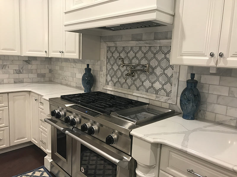 White Quartz with large vein pattern - close up of gas range and surrounding counter tops